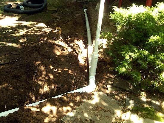 Downspouts Attached to an Under ground PVC Drainage System Helps to Relieve Erosion Issues